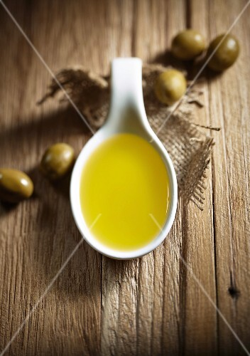 A spoonful of olive oil and green olives in the background