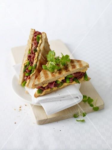 A roast beef and asparagus sandwich