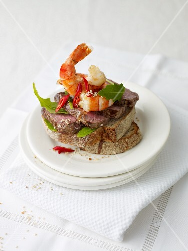 A slice of bread topped with beef and prawns