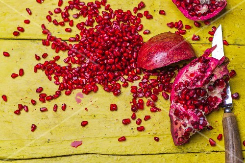 Pomegranates, whole and chopped, surrounded by seeds on a rustic yellow wooden surface