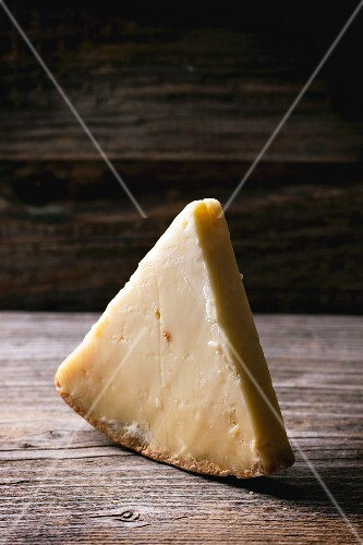 A piece of Belgian cheese on a wooden table