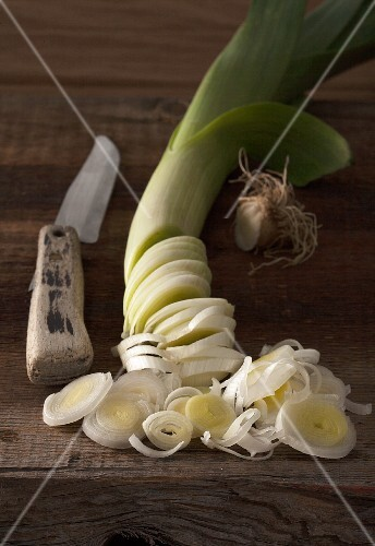 An arrangement of leek and an old vegetable knife on a rustic wooden table