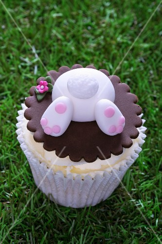 An Easter bunny cupcake on a grass surface