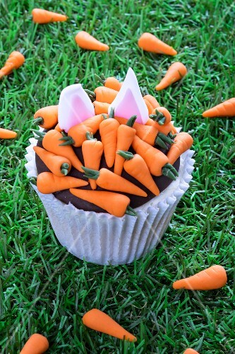 An Easter cupcake decorated with carrots and rabbit ears