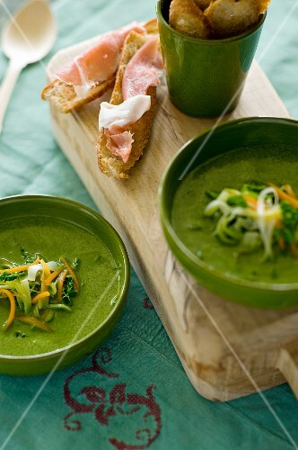 Green vegetable soup and slices of bread topped with ham
