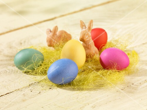 COlourful Easter eggs and terracotta Easter bunnies in decorative grass