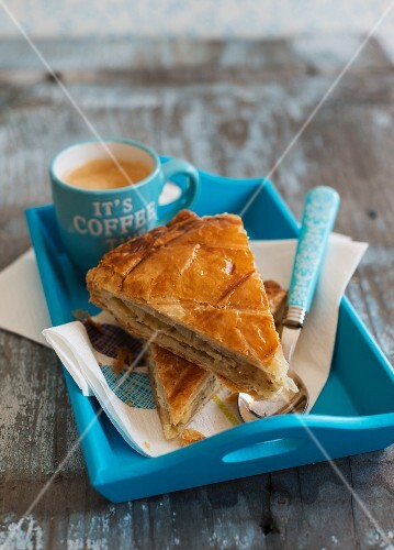 Two slices of galette des rois and coffee on a tray