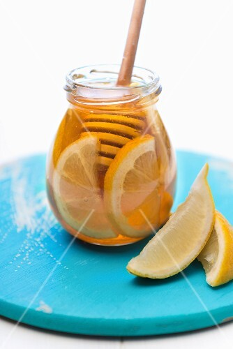 A jar of honey with lemon slices