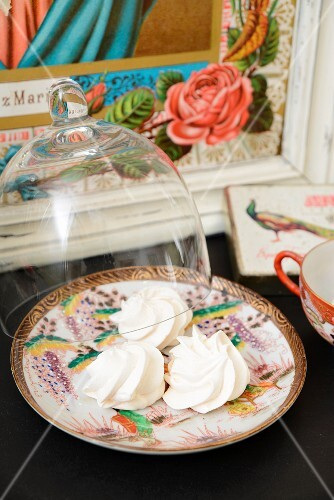 Meringues on a Chinese porcelain plate with a glass cloche and a picture of a saint in the background