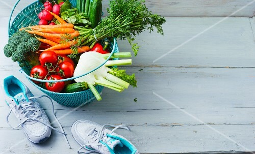 A shopping basket of vegetables with running shoes next to it