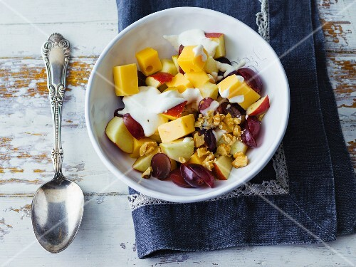 Cheese and fruit salad with chopped walnuts and sour cream