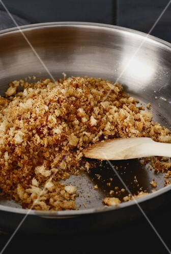 White bread crumbs being fried in butter