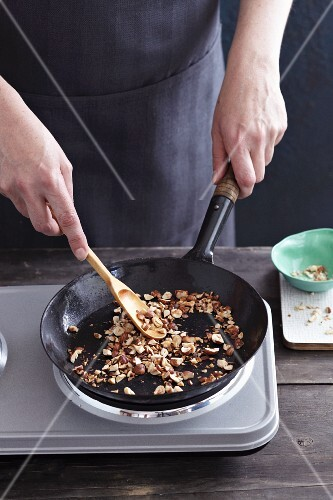 Chopped hazelnuts being dry roasted