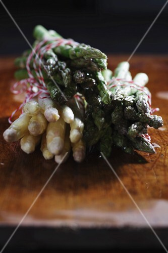 Bundles of white and green asparagus on a chopping board