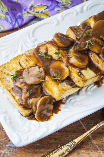 Fried tofu with thyme and a mushroom sauce