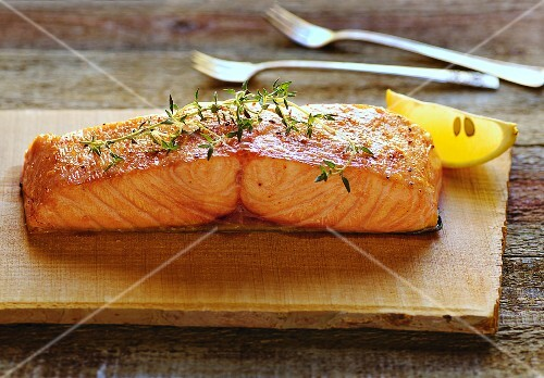 Roasted salmon with thyme on a chopping board