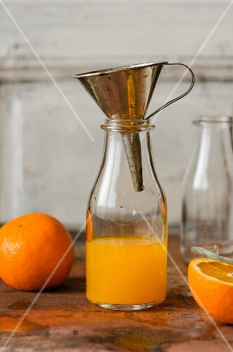 Freshly squeezed orange juice in a glass bottle with a funnel
