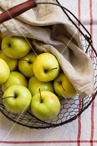 Green apple in a wire basket with a cloth