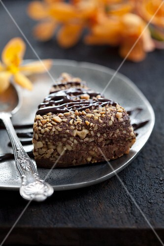 A slice of nut cake with a silver spoon on a plate