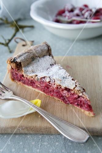 A slice of raspberry cake with frozen blackberries