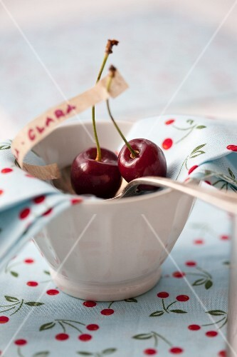 Cherries on a silver spoon in a bowl lined with a napkin