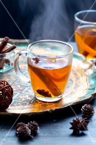 Cider punch with star anise and cinnamon stick in a tea cup