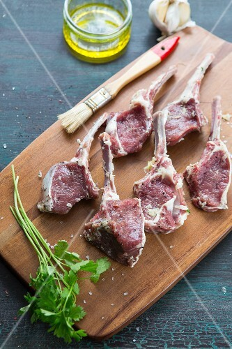 Raw lamb chops on a chopping board with garlic, olive oil and coriander next to it