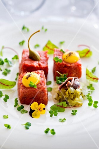 Beef tartare with caper fruits and egg yolks served with a gherkin and anchovy salad