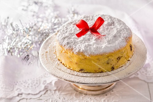 A Polish Christmas cheesecake decorated with a red bow on a silver cake stand