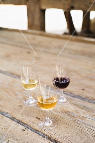 Two glasses of Riesling and a glass of pinot noir from vineyard Frick on a wooden table