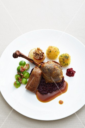Goose leg with red cabbage, potato dumpling, baked apples and Brussels sprouts
