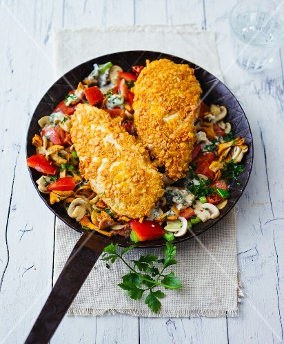 Chicken breast coated with soya flakes in a pan of fried mushrooms and vegetables