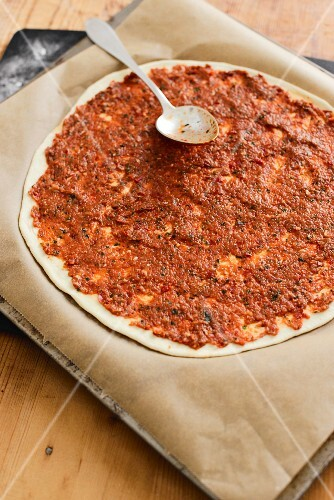 An unbaked lahmacun (a yeast dough pizza base topped with minced lamb, pepper purée and spices, Turkey)