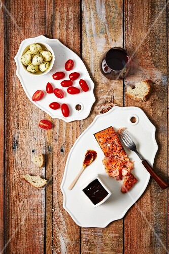 An anti pasti platter with salmon, tomatoes, artichokes, bread and red wine