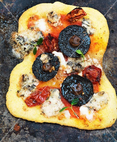 A pizza with mushrooms, blue cheese and tomatoes