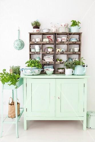 Herbs and kitchen utensils arranged on vintage, lime-green dresser