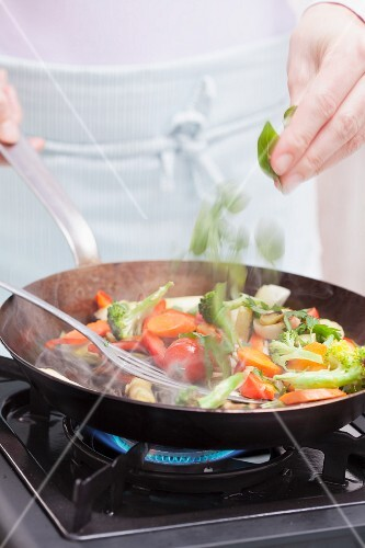 Fresh herbs being added to a steaming pan of vegetables