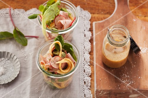 Leberkäse (beef and pork meatloaf) salad with omelette strips and fresh radishes served in jars