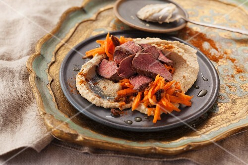 Fried lamb fillets with a carrot salad and hummus