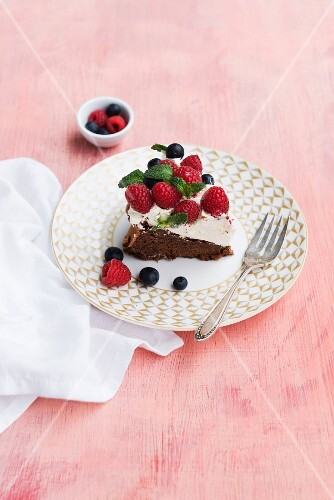 A slice of chocolate cake with cream and fresh berries