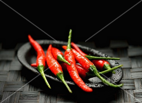 Fresh red chilli peppers on a black plate