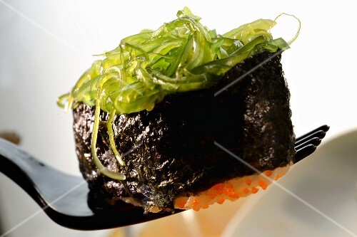 A maki sushi with glass noodles on a fork (close-up)