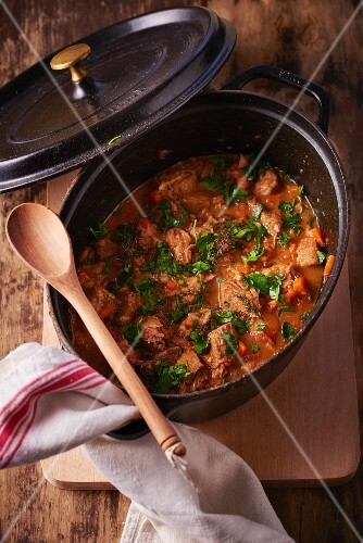 Veal goulash with parsley in a braising pot