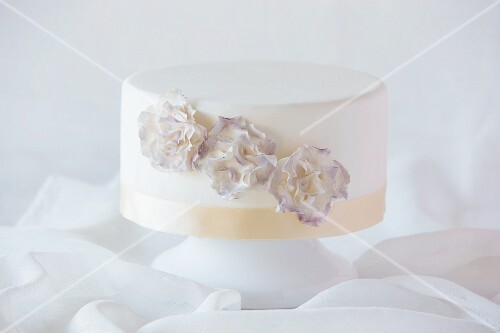 A white wedding cake decorated with flowers