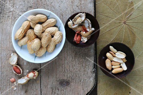 Peanuts, shelled and unshelled, in various bowls on a rustic board