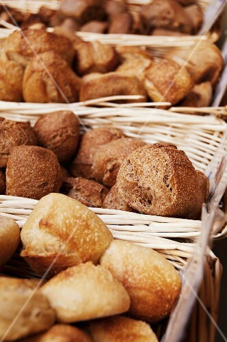 Various bread rolls in baskets in a bakery