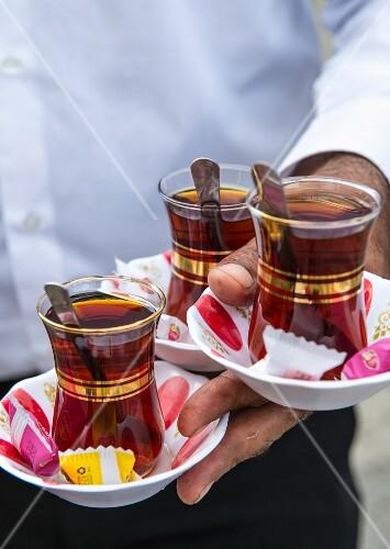 Three glasses of Turkish tea being served