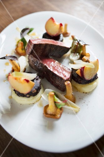 Rare saddle of venison with long pepper, vineyard peaches and fresh chanterelle mushrooms, pine black pudding at the restaurant 'Le Bambou' in Freiberg