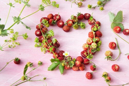 A heart-shaped wreath made from wild strawberries with lady's mantle in the background
