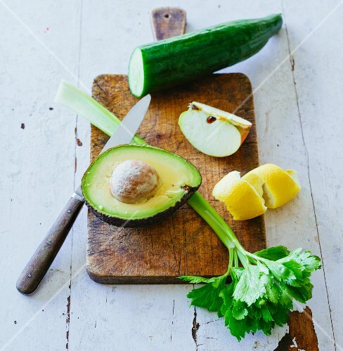 Ingredients for green smoothies: avocado, celery, lemon zest, apple and cucumber on a chopping board
